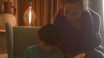 Frau, die sich dem Jungen anschließt, der Hausaufgaben im Sessel macht foto