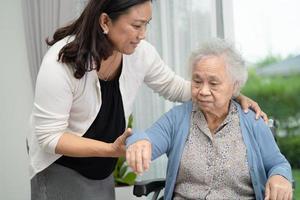 Hilfe und Pflege asiatische ältere Patientin, die im Rollstuhl sitzt foto