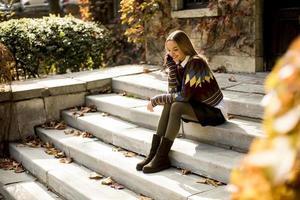 junge Frau sitzt auf einer Treppe mit Handy im Herbstpark foto