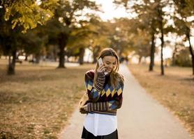 hübsche junge frau, die im herbstpark spaziert und ein handy benutzt foto