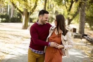 junge Frau und Mann, die Händchen haltend im Stadtpark spazieren gehen foto