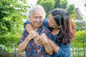 asiatische ältere frau mit pflegerin, die mit glücklich im naturpark spaziert. foto