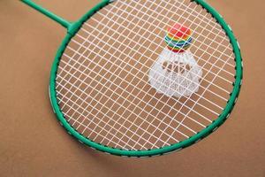 Badmintonschläger und Federball auf braunem Hintergrund und Kopierraum foto