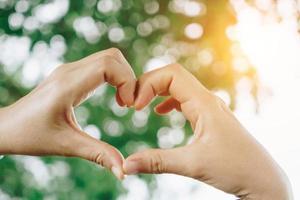 Frauenhand tun Herzform auf grüner Bokeh-Natur. foto