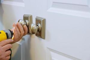 Meister mit Schraubendreher installiert Tür neues Dummy-Schloss im Haus. foto