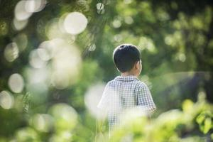 Nahaufnahme der Rückseite des kleinen Jungen, der im Park spazieren geht. foto