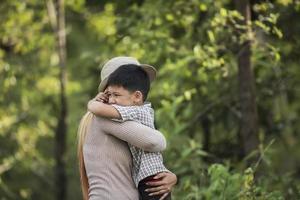 Porträt von Mutter und Sohn glücklich zusammen im Park kuscheln. foto
