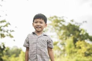Porträt des kleinen Jungen, der im Naturpark steht und zur Kamera lächelt. foto