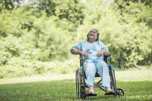 einsame ältere Frau sitzt im Rollstuhl im Garten im Krankenhaus foto