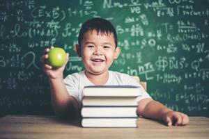 Junge hält einen Apfel im Klassenzimmer foto