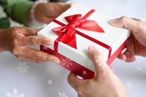 Nahaufnahme von Händen, die Geschenkbox an Weihnachten und Neujahr geben? foto