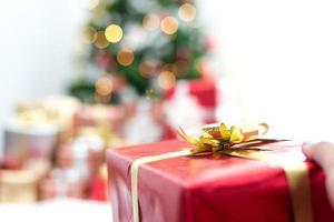 Hand hält Geschenk in Weihnachtsfeier. Weihnachts- und Silvesterparty foto