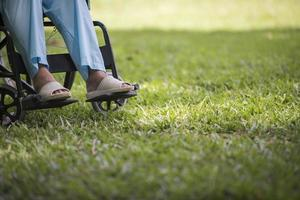 Nahaufnahme einer einsamen älteren Frau, die im Rollstuhl im Garten sitzt foto