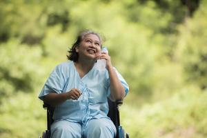 Alte Frau sitzt mit Wasserflasche im Rollstuhl, nachdem sie ein Medikament eingenommen hat foto