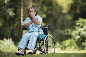 einsame ältere frau, die trauriges gefühl im rollstuhl im garten sitzt foto