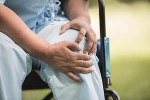 ältere Frau, die mit Knieschmerzen im Rollstuhl sitzt foto