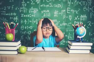 besorgtes Mädchen im Klassenzimmer mit den Händen auf dem Kopf foto