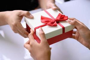 Nahaufnahme von Händen, die am Weihnachtstag eine Geschenkbox mit rotem Band geben? foto