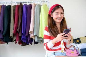 asiatischer vlogger blogger, der frau kleidertasche online mit telefon verkauft foto