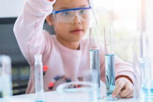 Asiatisches kleines Mädchen, das blaue Lösung im Reagenzglas hält und fallen lässt foto