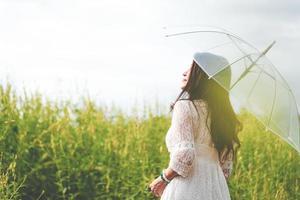 Asiatin im weißen Kleid mit Regenschirm im Rapsfeld foto