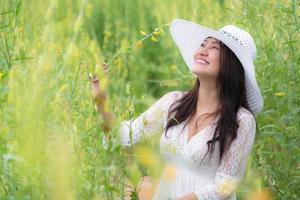 asiatische Frau im weißen Kleid Flügelhut zu Fuß in Rapsblumenfeld foto