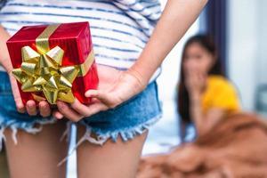 Nahaufnahme von Frauenhänden mit Geschenk überraschen ihre Freundin Schlafzimmer foto