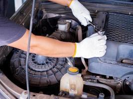 Mechaniker, der einen Blockschlüsselgriff hält, während er ein Auto repariert. foto