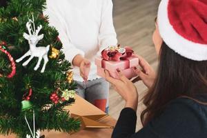 Mutter gibt ihrer kleinen Tochter in den Weihnachtsferien Geschenke foto