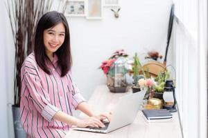 Porträt der jungen asiatischen Frau, die online am Laptop arbeitet. foto