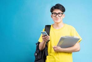 asiatische männliche studentenporträt, auf blauem hintergrund isoliert foto