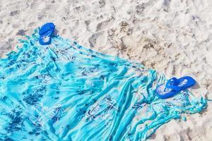 blaue Flipflops auf blauem Strandtuch auf weißem Sand. foto