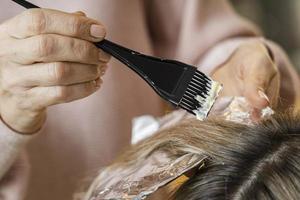 Frau lässt sich von Kosmetikerin die Haare färben foto