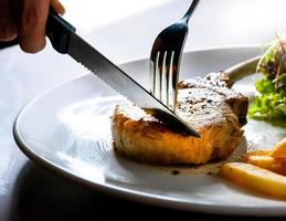 Messer schneiden gegrilltes Schweinekotelett Steak foto