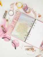 rosa Planer mit süßem Briefpapier zum Fotografieren im Flatlay-Stil foto