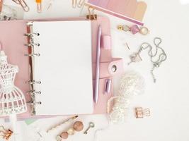Draufsicht auf einen rosa Planer mit süßem Briefpapier foto