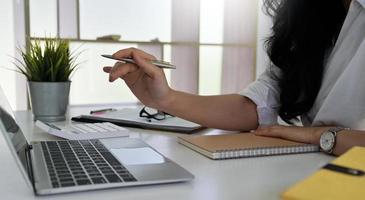 Frau, die einen Stift in der Hand hält und auf einen Laptopbildschirm zeigt. foto