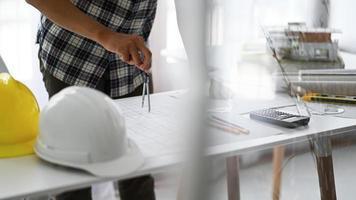 Designer verwenden Kompasse, um Entwürfe auf Hausplänen zu zeichnen. foto