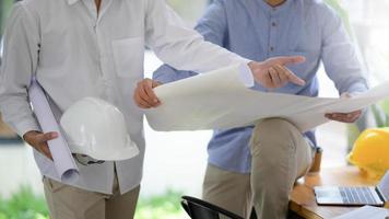 Designer und Bauherren sehen sich Hauspläne an, um die Bauarbeiten zu planen. foto
