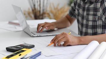 Mann benutzt einen Bleistift, um auf dem Hausplan zu schreiben. foto