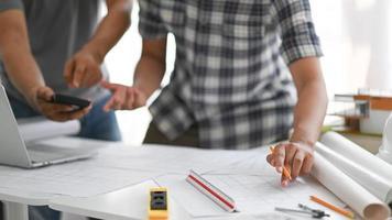 Architekten, die Bleistifte und Taschenrechner halten, überprüfen den Hausplan. foto