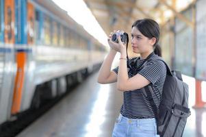 Während sie auf einen Zug wartet, trägt eine junge ausländische Besucherin eine Kamera, um Fotos zu machen.