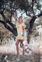 eine barfüßige blonde Frau in einem gelben Sommerkleid foto