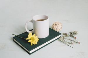 Tasse und Blume auf einem Notizbuch foto