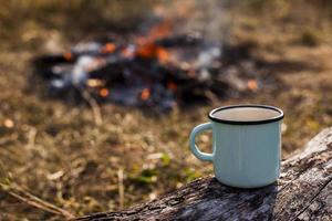 blaue Tasse Kaffee am ausgebrannten Lagerfeuer foto