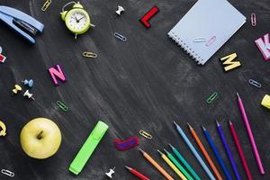 Schulpapier mit Apfel und Wecker auf verstreuter Tafel foto