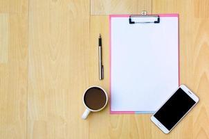Mockup Telefon Kaffeetassen Kopfhörer Notizpapier auf einer hölzernen Draufsicht platziert foto