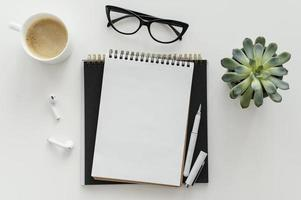 Anordnung mit leerem Notizblock auf dem Schreibtisch foto