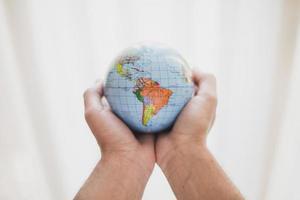 Mann hält kleinen Globus foto