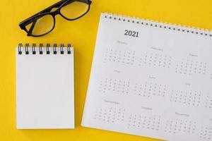 Kalender mit Notizblock und Brille foto